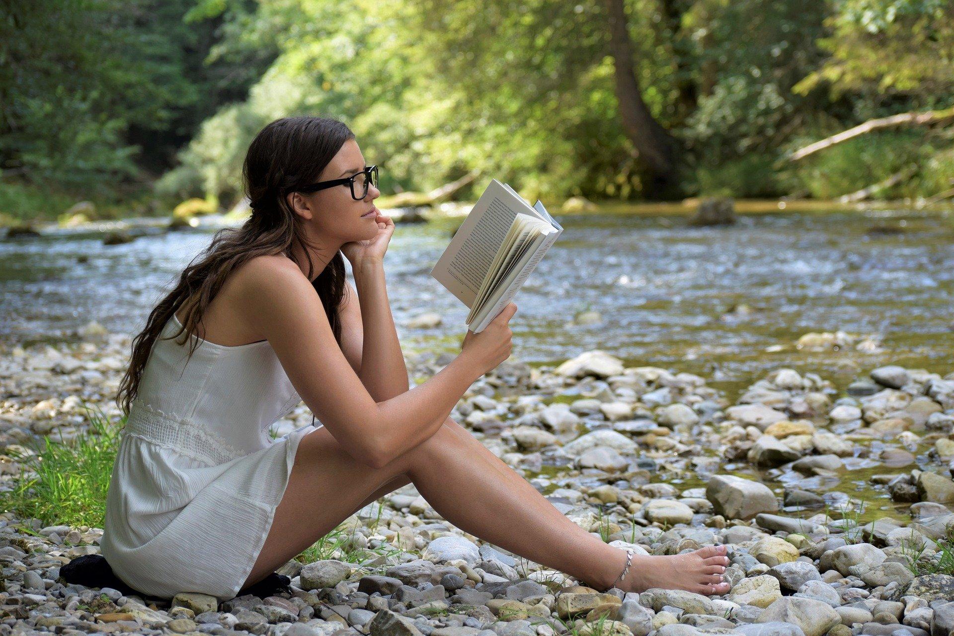 Auf steinigem Untergrund in einem Buch dem Sinn des Lebens nachspüren.