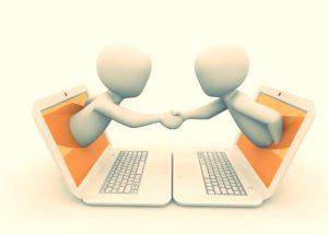 Zwei weiße Männchen geben sich die Hand. Jeder schaut aus einem weißen Laptop mit orangefarbenem Desktop. Das Licht wirkt etwas goldfarben.