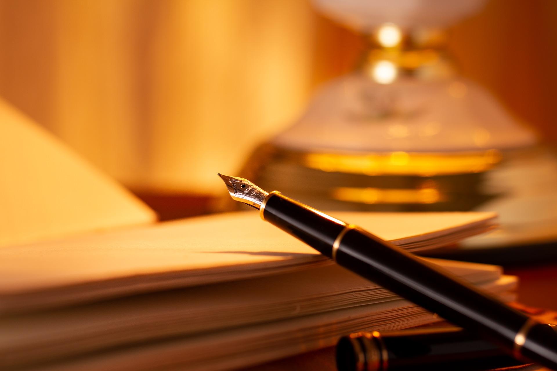 Traumdeutung: Ein Notizbuch mit offenem Füllfederhalter. Alles ist in gelbes Licht getaucht.