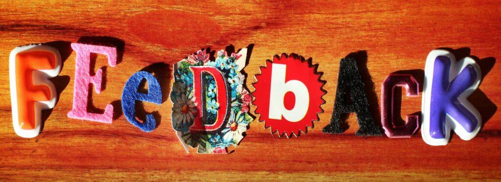 Coaching-Feedback: Auf rot-organgenem Holz bilden bunte Buchstaben aus Stoff und Filz das Wort Feedback.