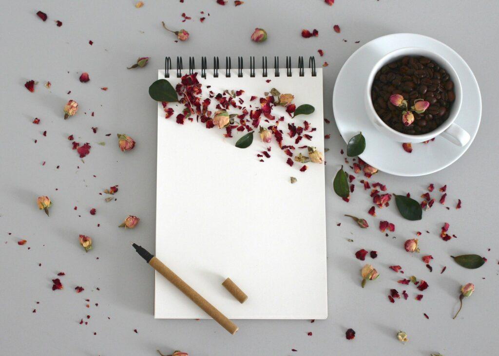 Ein weißer Schreibblock mit violetten Blüten bestreut. Daneben eine Tasse mit Kaffee, in der einige Blüten schwimmen. Notizen zum Dankbar sein.