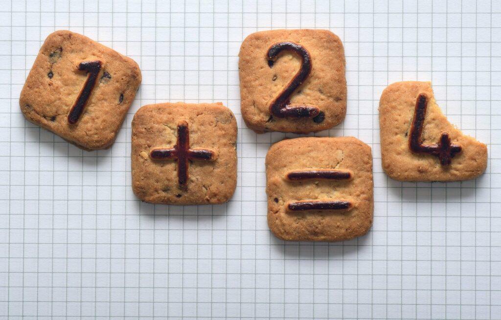 Vier Kekse zeigen die Rechenaufgabe 1+2=5. Der Keks mit der 4 ist an einer Ecke angebissen. Dankbar sein?