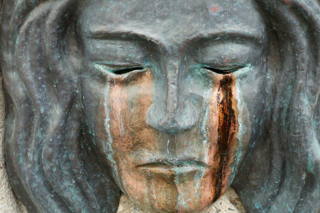 Akzeptanz mit Tränen: Gesicht aus Bronze, Tränen, Traurigkeit